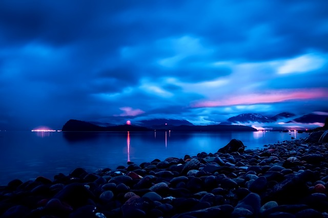 View of Juneau, Alaska shoreline at dusk with sun setting and dense clouds above city lights
