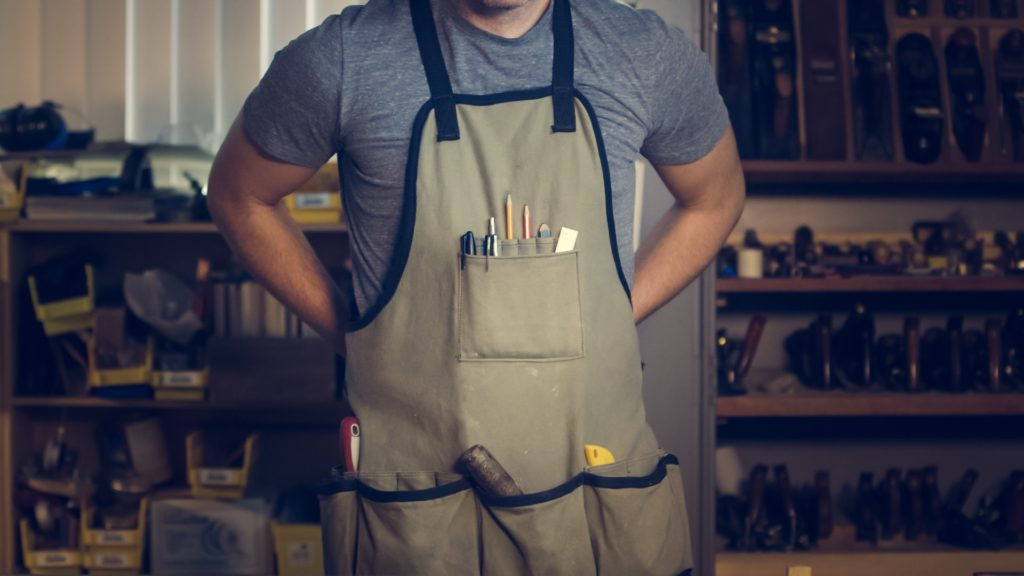 A plumber stands in front of a workbench while putting on an apron filled with tools.