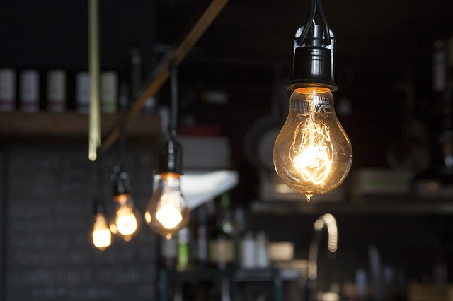 Four light bulbs hang from a ceiling beam. One is prominently displayed in the foreground.