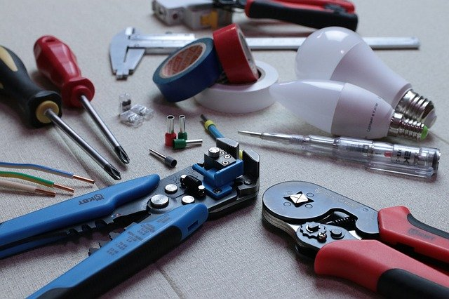 Various tools, wiring, tape, and lightbulbs are placed in a group.