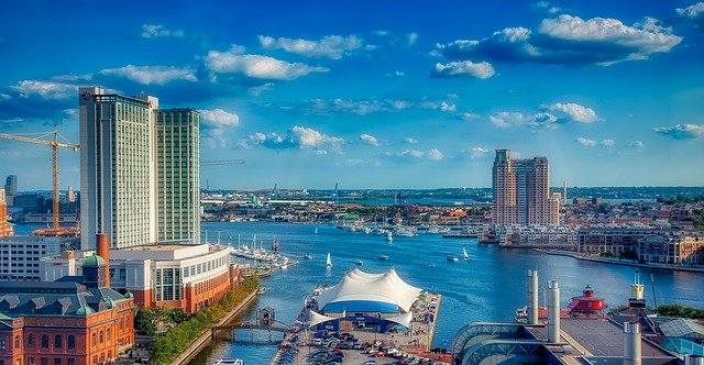 A photo of Harbor Bay in Baltimore, Maryland, featuring the bay, skyscrapers, and several historic buildings.