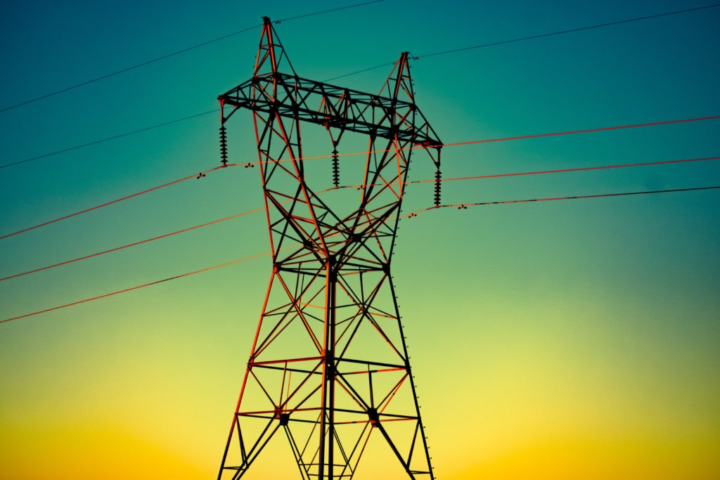 A transmission tower against a gradient background.