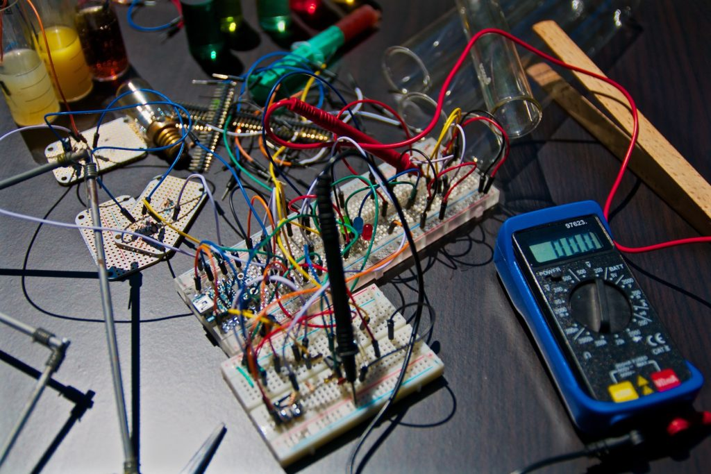An image of an electronic circuit board next to a tester.