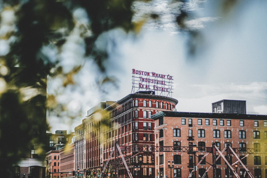 """A photo of an urban street and building. The top of the building has a sign that states """"Boston Wharf Co. Industrial Real Estate""""."""