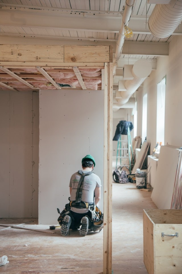 A general contractor kneeling before a wall frame in a house.