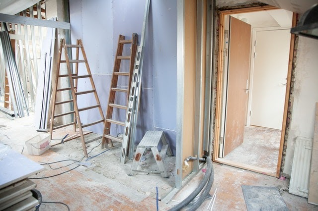 A room in the midst of being remodeled with ladders and siding scattered throughout.
