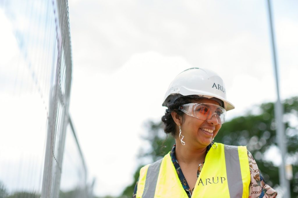 An engineer in a hard hat and safety vest smiling on a construction site.